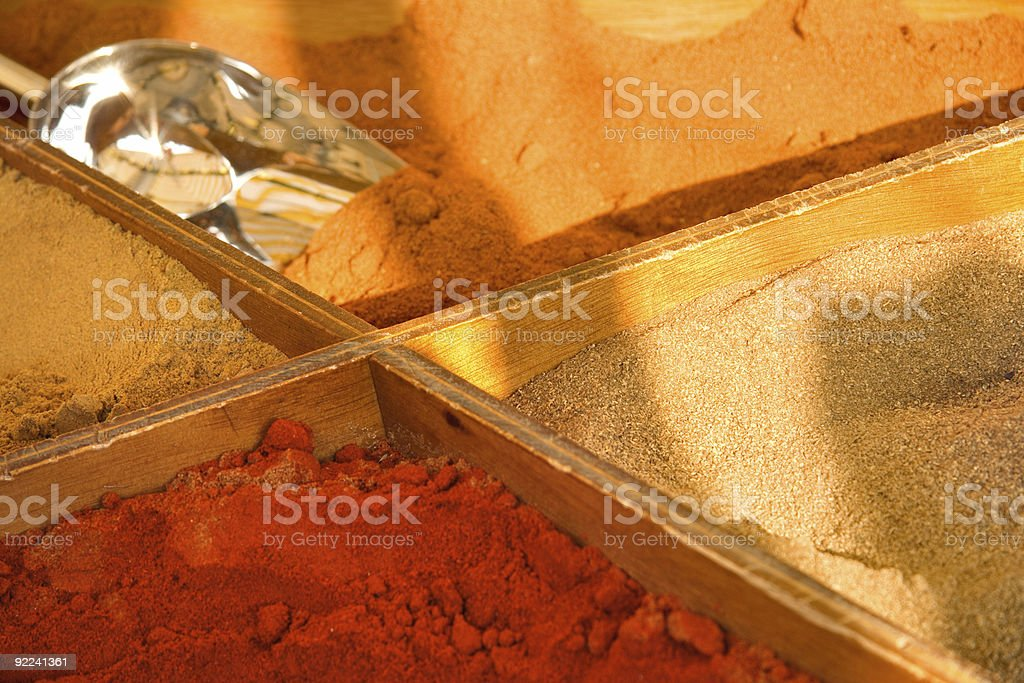 four bright color spices in a market stock photo