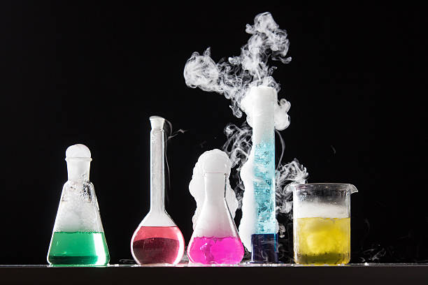 Four bubbling beakers of colorful liquid