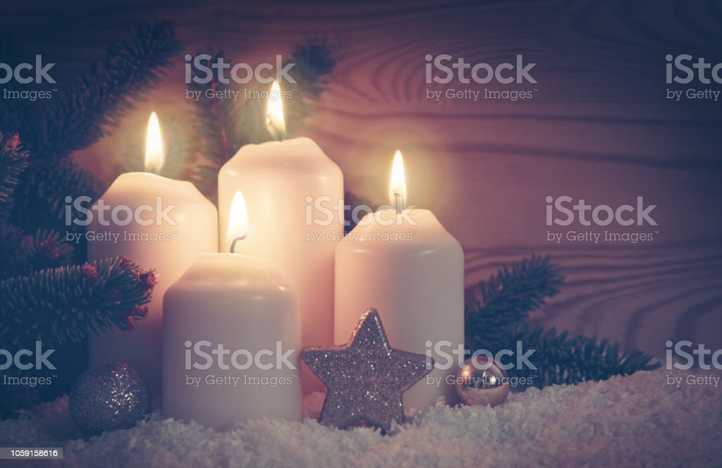 Christmas background with four white advent candles and golden...