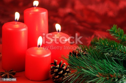 Four red Advent candles are burning. Aside laying pine cone and twig with star anise. On table with red tablecloth. Soft focus on first candle. Useful Christmas background for greeting card.