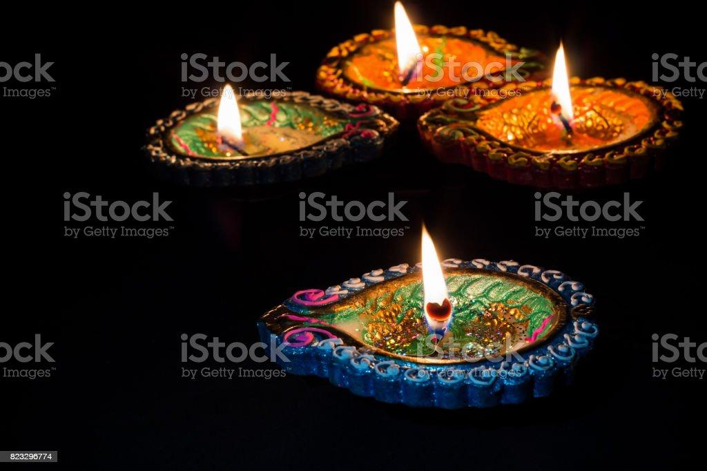 Quatro colorido a queimar velas estilo indiano para o celebration de Diwali em fundo preto. - foto de acervo