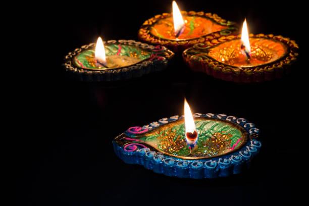 Vier bunte brennen Kerzen indischen Stil für Diwali Feiern auf schwarzem Hintergrund. – Foto