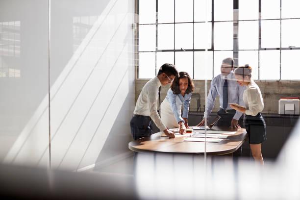 czterech kolegów biznesowych stoi na czacie w sali konferencyjnej - selektywna głębia ostrości zdjęcia i obrazy z banku zdjęć