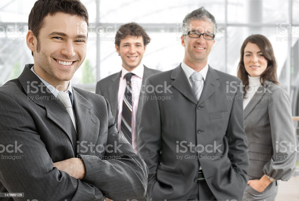 Four business partners smiling and posing for camera royalty-free stock photo