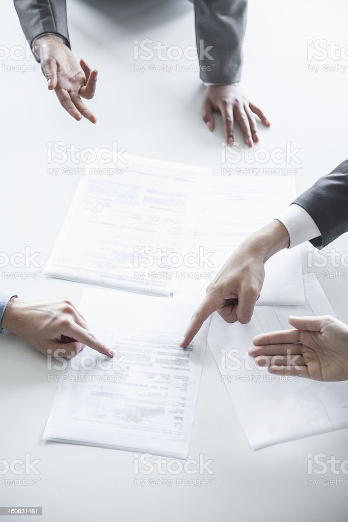 Four business people arguing and gesturing around a table stock photo