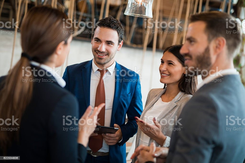 Four business people discussing business strategy using digital tablet ストックフォト