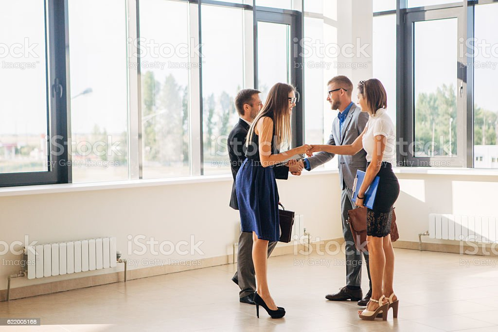 four business people handshake in office lobby stock photo