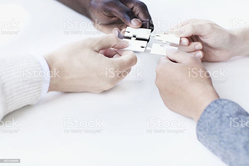 Four business people holding jigsaw puzzle pieces stock photo