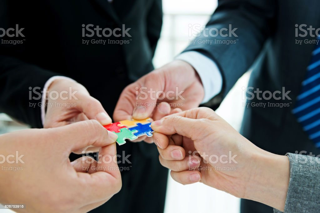 Four business people holding puzzle pieces stock photo