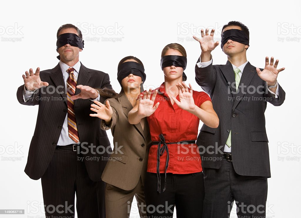 Four business people in blindfolds holding out their arms stock photo