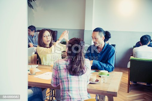 istock Four business people meeting in a cafe 584889582
