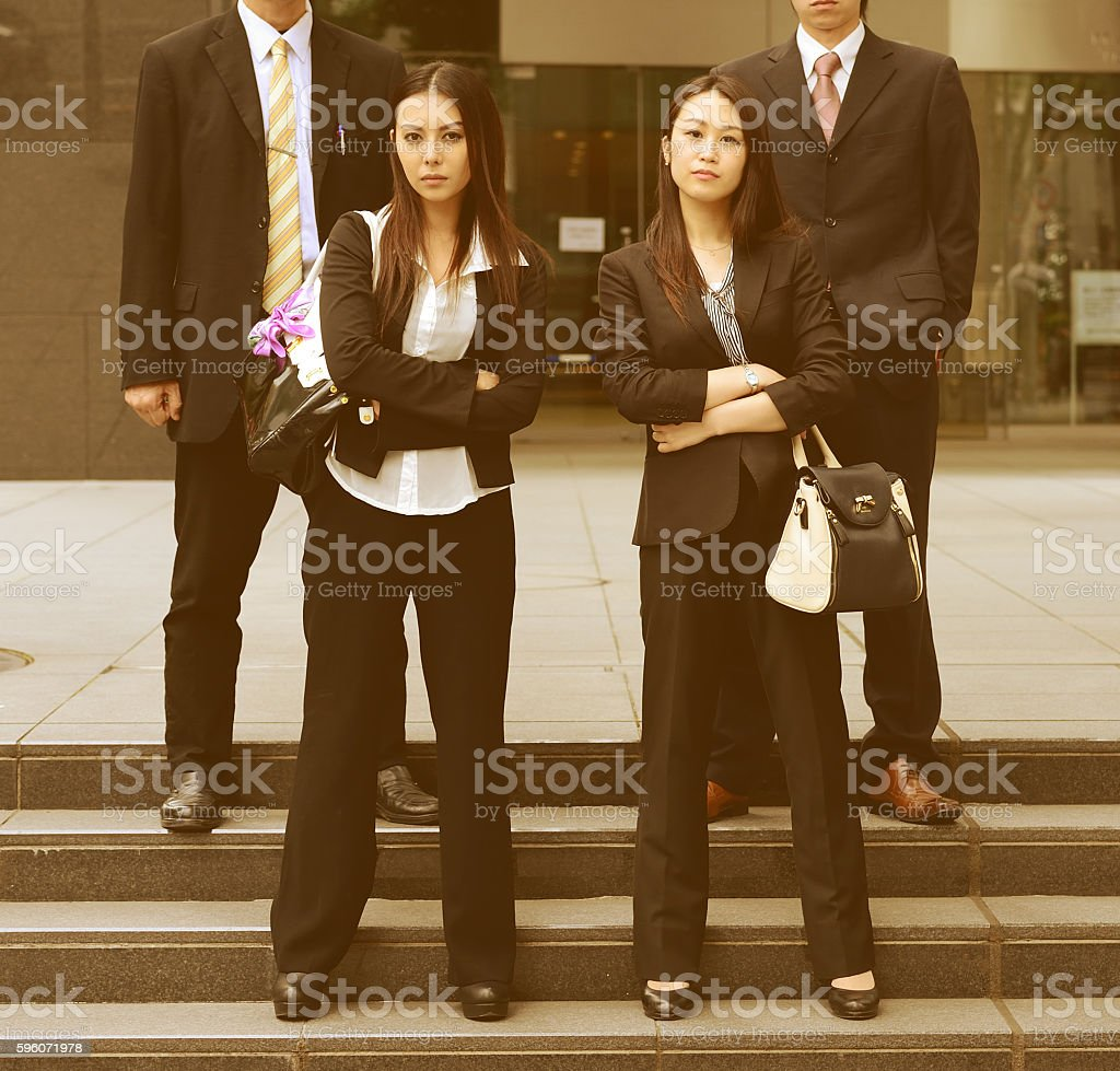 Four business people posing for camera, focus on women royalty-free stock photo