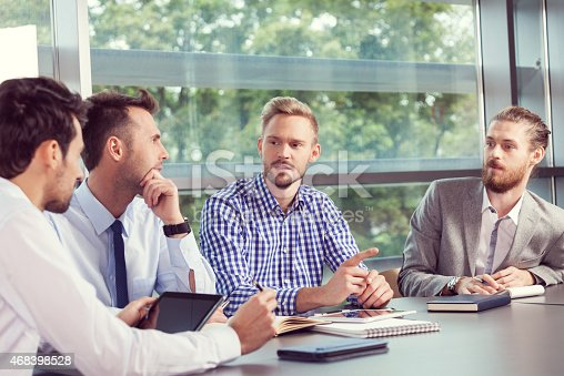 istock Four businessmen discussing in a meeting room 468398528
