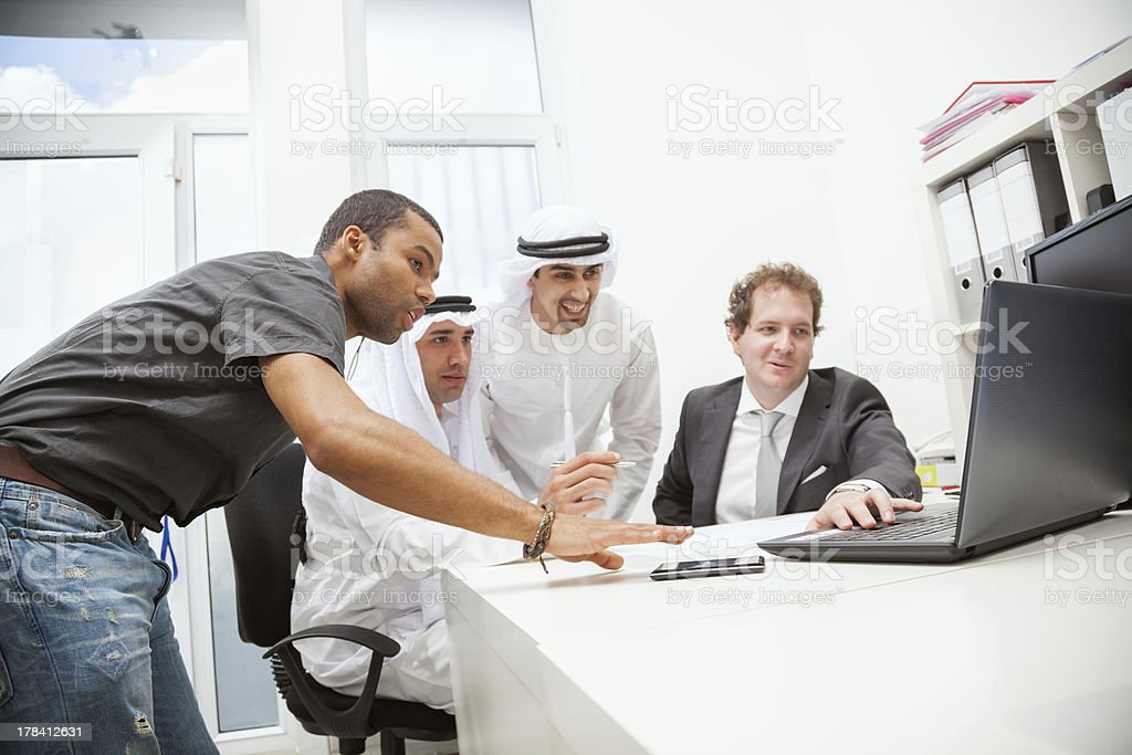 Four businessmen on a desk working with a laptop stock photo