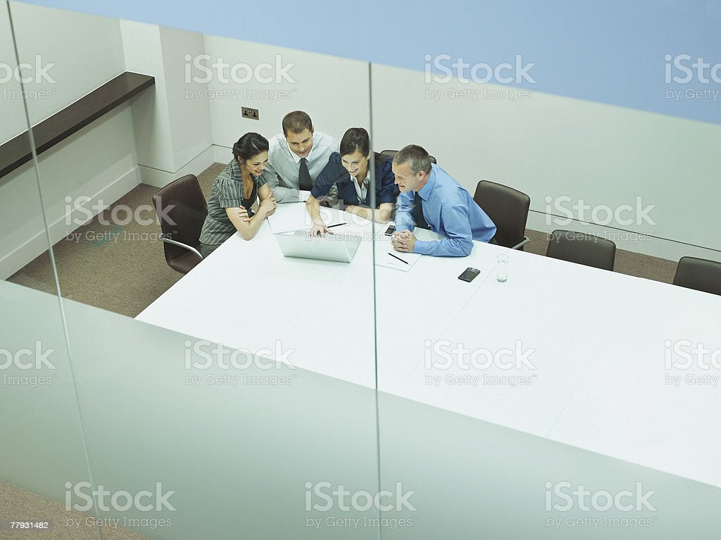Four businesspeople at a table with documents and laptop royalty-free stock photo