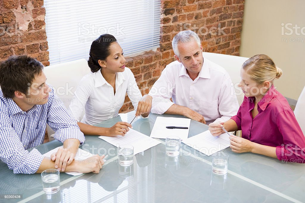Four businesspeople in boardroom talking royalty-free stock photo
