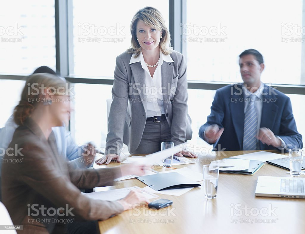 Four businesspeople in boardroom with one in focus stock photo