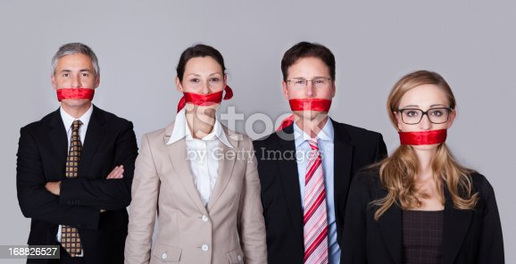 istock Four businesspeople with red tape around their mouths 168826527