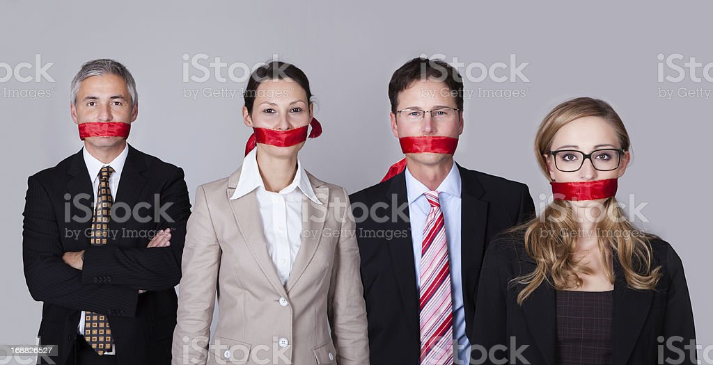 Four businesspeople with red tape around their mouths stock photo