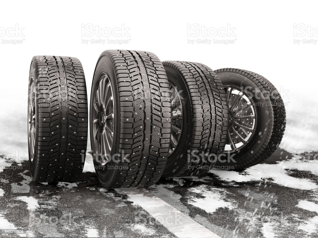 Four car tires rolling on a snow-covered road. stock photo