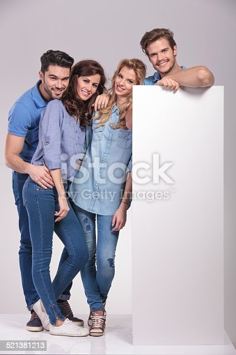 istock four casual young people with a big blank billboard 521381213