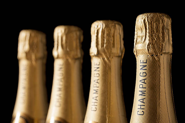 Four champagne bottles with gold wrappings stock photo