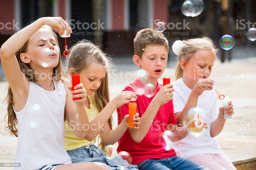 Four cheerful kids blowing soap bubbles stock photo