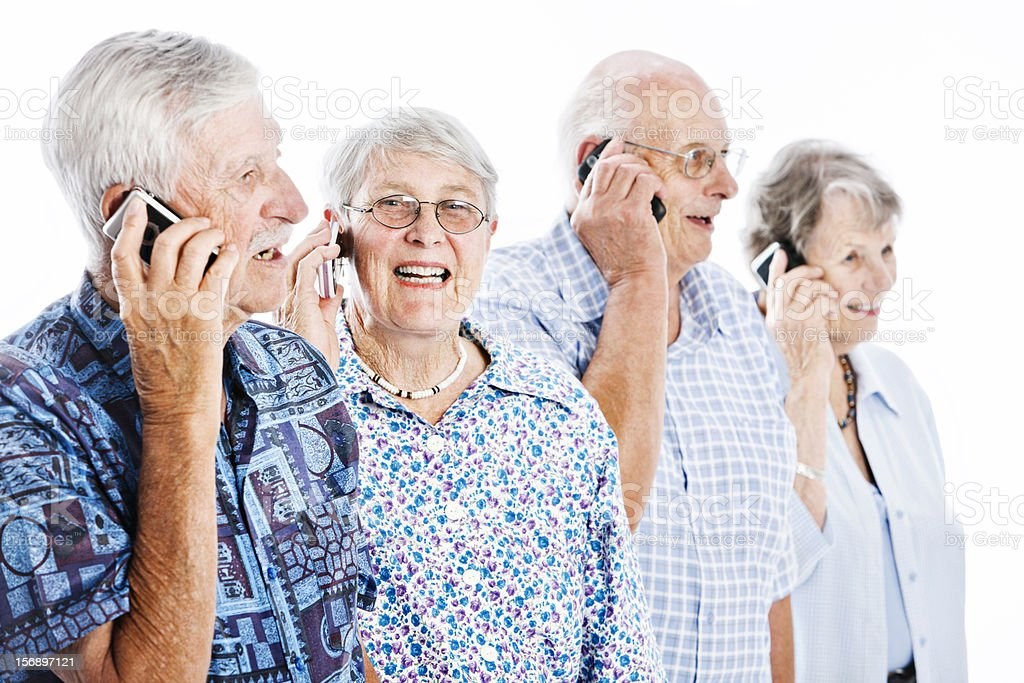 Four cheerful seniors chat on mobile phones royalty-free stock photo
