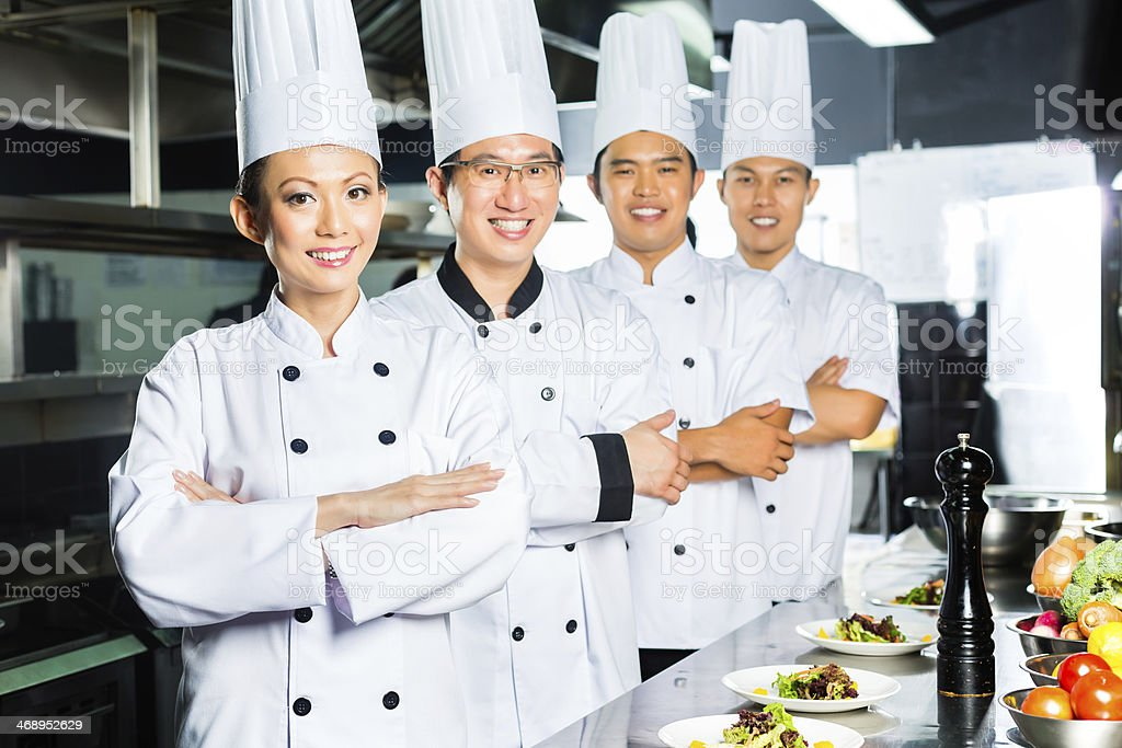 Four chefs in an restaurant kitchen crossing their arms  stock photo