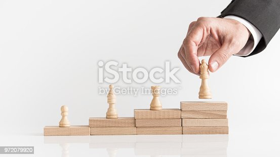 istock Four chess pieces on a stepped stack of blocks 972079920