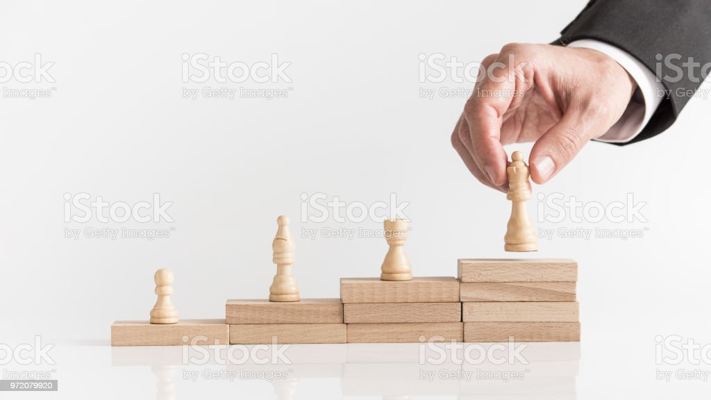 Four chess pieces on a stepped stack of blocks stock photo