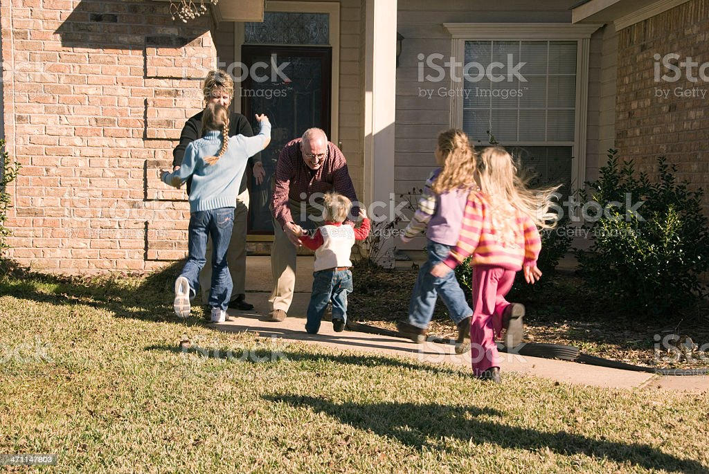 Four children eagerly running to greet their grandparents stock photo