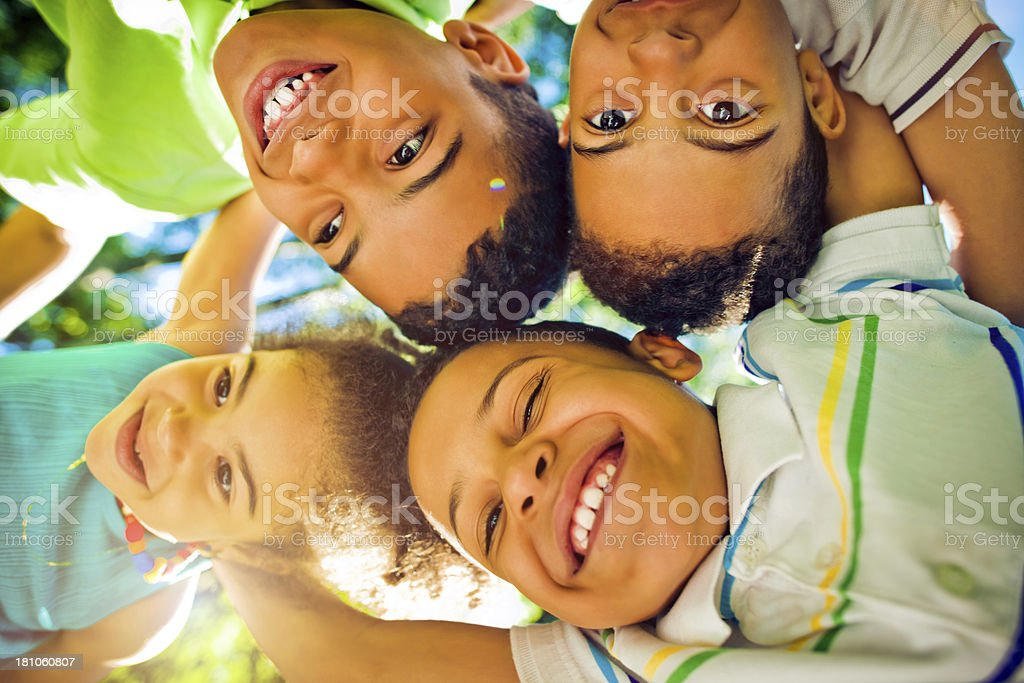 Four children hugging outdoors royalty-free stock photo