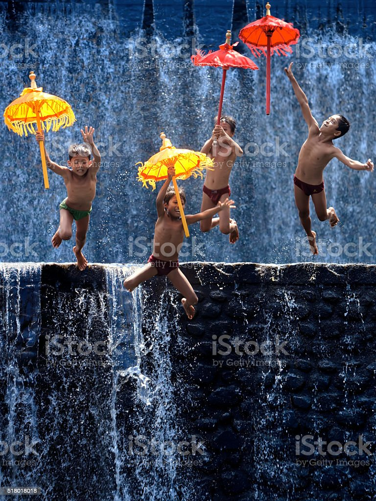 Four Children Jump With Umbrellas stock photo