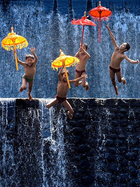 Four Children Jump With Umbrellas stock photo