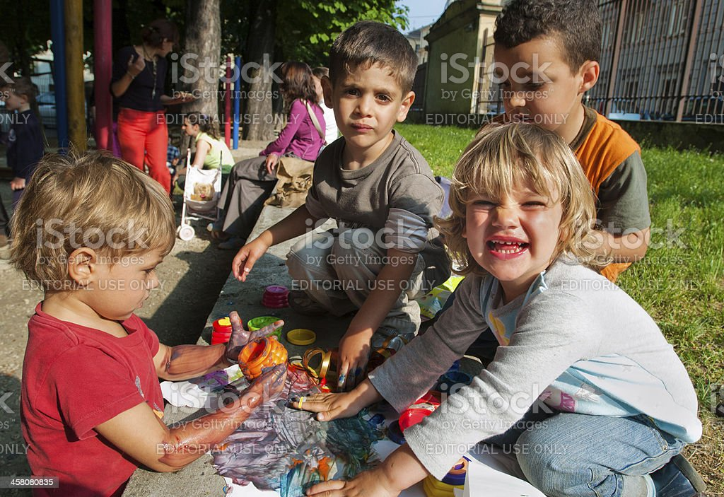 Four children (preschool age) playing with colours in a park stock photo