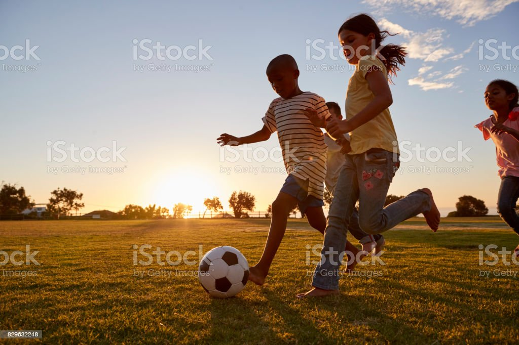 Four children racing after a football plying on a field stock photo