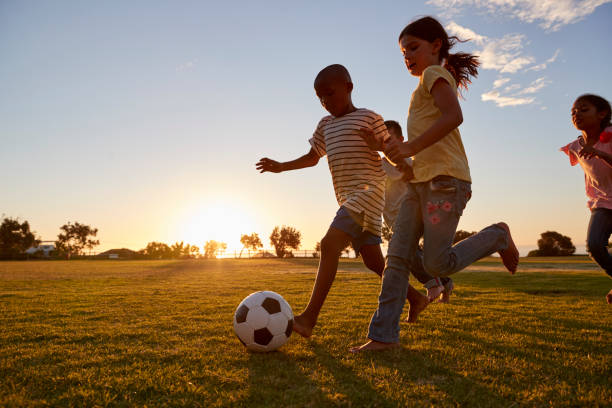 four children racing after a football plying on a field - messing about stock photos and pictures