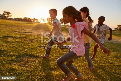 istock Four children running barefoot in a park 829630084