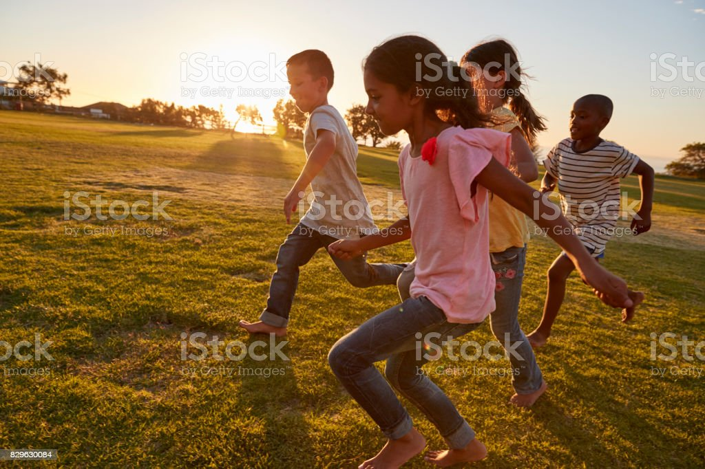 Four children running barefoot in a park stock photo