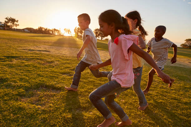 four children running barefoot in a park - messing about stock photos and pictures
