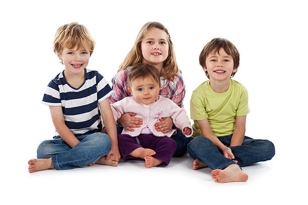 Four children sitting on white background smiling stock photo