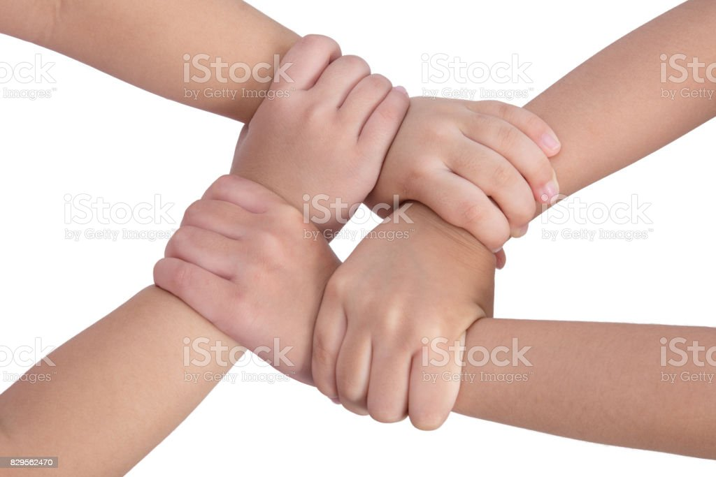 Four child's hands crossed and holding each other stock photo