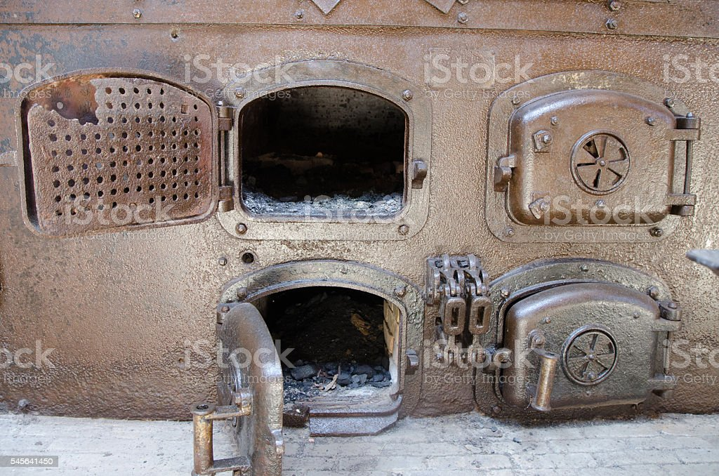 Four coal rusty furnaces with doors opened and closed stock photo