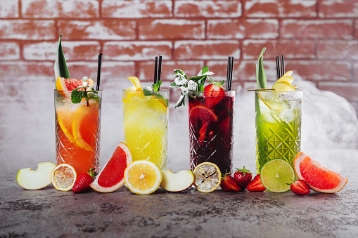 Four cocktails on table with fruits in smoke.