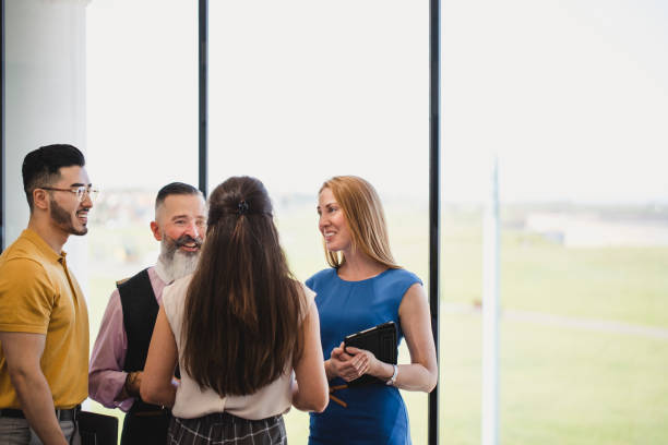 Four colleagues socialising by window at business event