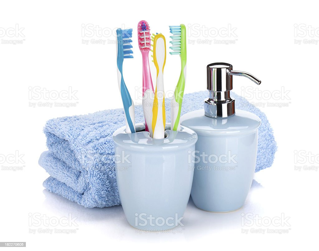 Four colorful toothbrushes, liquid soap and towel royalty-free stock photo