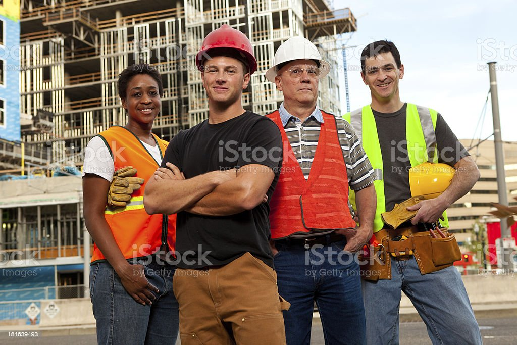 Four construction workers standing in front of a building site. royalty-free stock photo