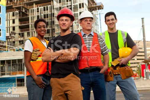 istock Four construction workers standing in front of a building site. 184639493