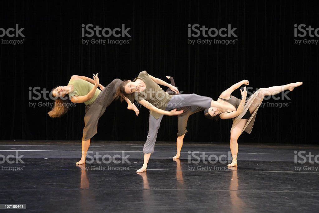 Four contemporary dancers kicking while performing on stage stock photo